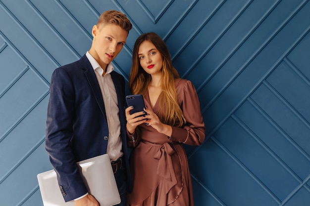 Stijlvolle jonge kerel met laptop en meisje met telefoonemoties, aquaachtergrond Premium Foto