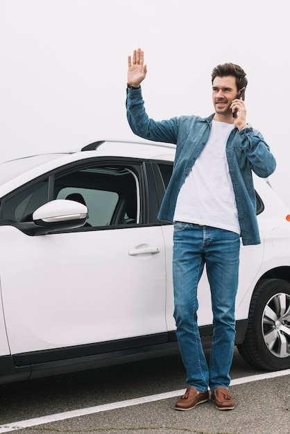 Stijlvolle jonge man die in de buurt van de moderne auto zwaait met zijn hand Gratis Foto