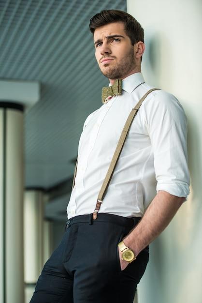 Stijlvolle jonge man is poseren in modern gebouw. Premium Foto