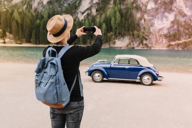 Stijlvolle jonge man met trendy hoed plezier op de oever van het meer en het maken van foto van landschap, mobiele telefoon vast te houden Gratis Foto