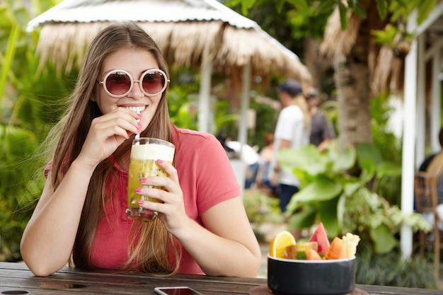 Stijlvolle jonge vrouw dragen ronde tinten zittend aan de toog en fruit shake nippen met stro, ontspannen en genieten van zonnige dag tijdens vakantie in hete exotische land. Gratis Foto