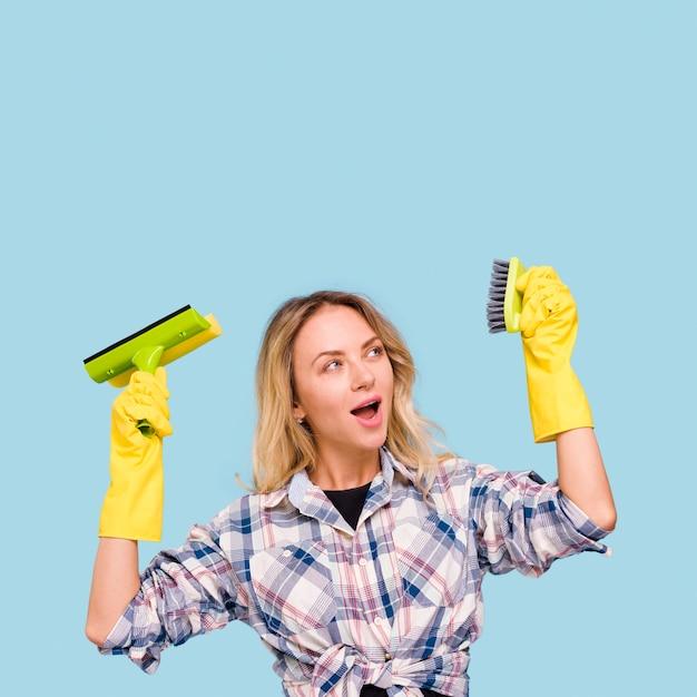Stijlvolle jonge vrouw houden en kijken naar reinigingsapparatuur met open mond Gratis Foto