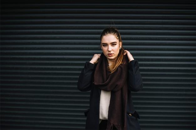 Stijlvolle jonge vrouw in jas met sjaal in de buurt van muur van geprofileerde platen Gratis Foto