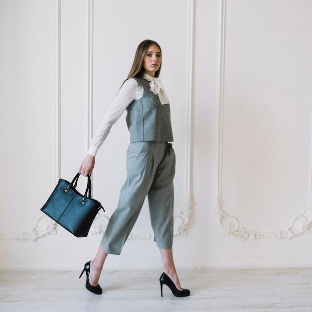 Stijlvolle jonge vrouw in kostuum met handtas in de kamer Gratis Foto