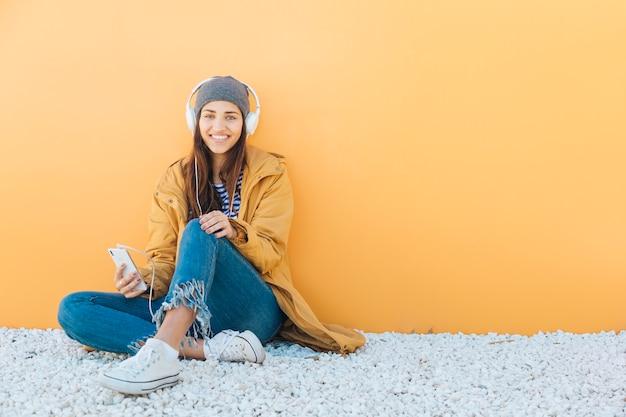 Stijlvolle jonge vrouw met behulp van mobiele telefoon dragen van koptelefoon zittend op tapijt Gratis Foto