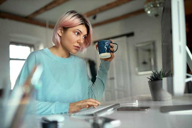 Stijlvolle jonge vrouw met roze haren zittend op haar werkplek te typen op het toetsenbord, het drinken van thee gebruiken Gratis Foto