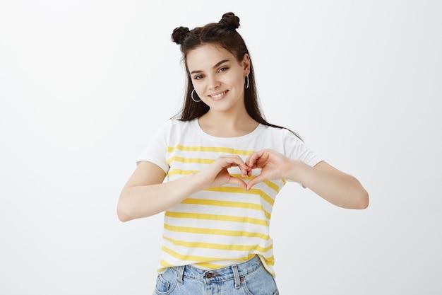 Stijlvolle jonge vrouw poseren tegen witte muur Gratis Foto
