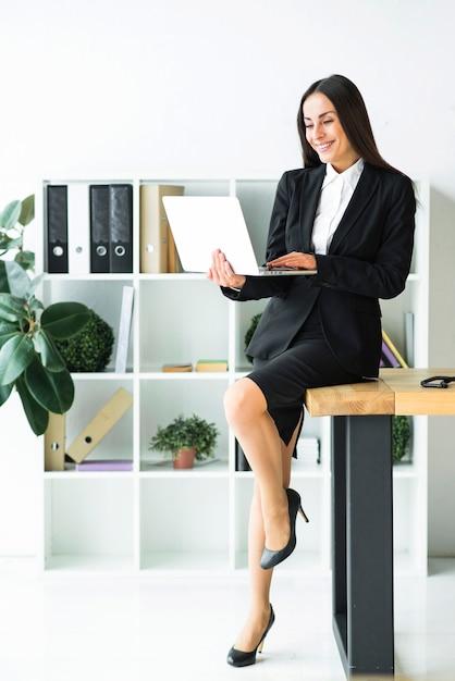 Stijlvolle jonge zakenvrouw zittend op een bureau met behulp van laptop Gratis Foto