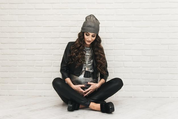 Stijlvolle jonge zwangere meisje in zwarte kleding met krullen op witte muur. foto's wachten op baby Premium Foto