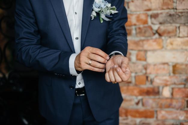 Stijlvolle jongeman die de manchetknopen op de mouwen dichtknoopt. stijl. Premium Foto