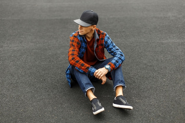 Stijlvolle jongeman in een zwarte pet, overhemd, spijkerbroek en sneakers zit op de stoep Premium Foto