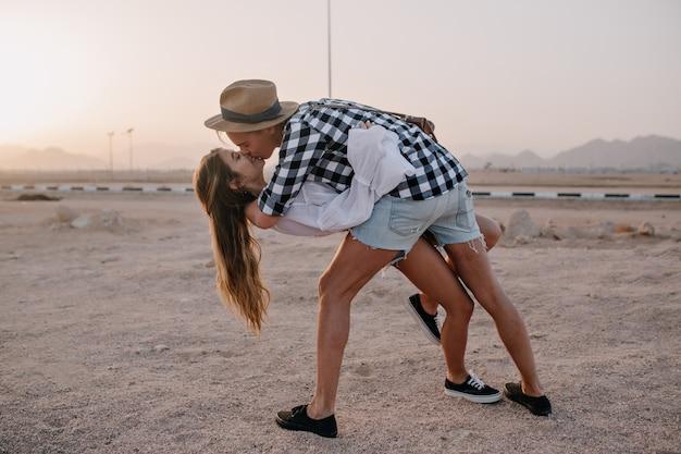 Stijlvolle jongeman in hoed en langharige slanke vrouw dansen op het zand en kussen bij zonsondergang. portret van een schattig omarmen paar in denim shorts, samen tijd doorbrengen op de berg Gratis Foto