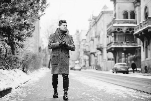 Stijlvolle jongeman in warme grijze jas en lederen handschoenen lopen in de straat. street style. street style. zwart-wit foto. Premium Foto