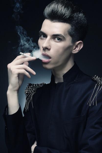 Stijlvolle jongeman roken van een sigaret Premium Foto