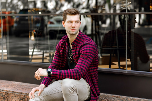 Stijlvolle knappe jonge zakenman zittend op straat, geweldige glimlach, bruine haren en ogen, hipster geruite shirt en beige broek, zonnebril en horloges dragen, poseren in de buurt van restaurant. Gratis Foto