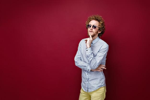 Stijlvolle krullendharige man in zonnebril op rode achtergrond. thinki Premium Foto