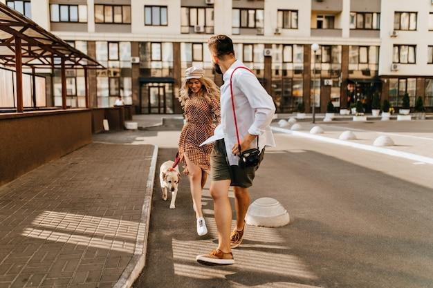 Stijlvolle man en vrouw in zomeroutfits rennen en spelen met hun hond op de achtergrond van het appartementencomplex. man in licht overhemd houdt zijn geliefde hand vast en draagt de camera. Gratis Foto