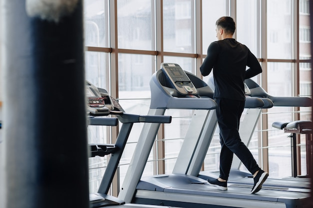Stijlvolle man in de sportschool traint op de loopband. gezonde levensstijl. Gratis Foto