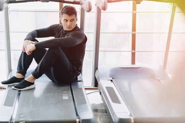 Stijlvolle man in de sportschool zit te rusten op de loopband. gezonde levensstijl. Gratis Foto