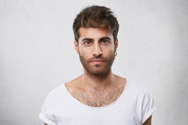 Stijlvolle man met baard, trendy kapsel, oorbel in het oor en wit t-shirt die direct met zijn donkere ogen kijkt Gratis Foto