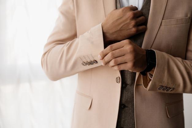 Stijlvolle man past een mouw van zijn jas aan Gratis Foto