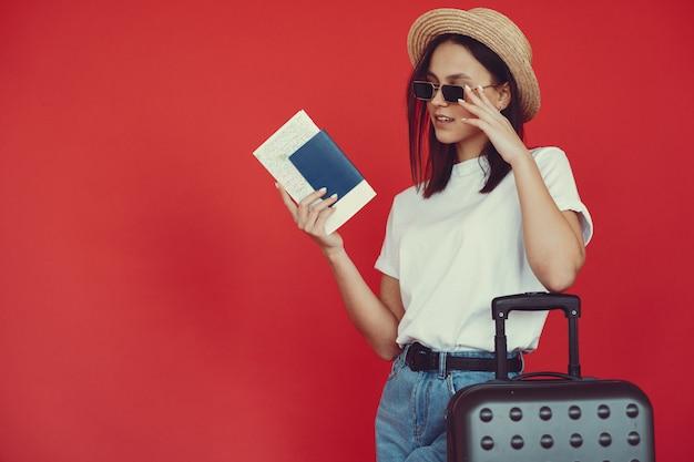 Stijlvolle meisje poseren met reisapparatuur op een rode muur Gratis Foto