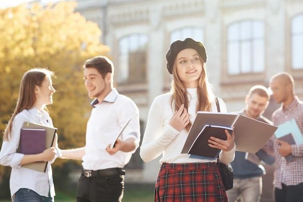 Stijlvolle meisje staat op de binnenplaats van de universiteit. Premium Foto