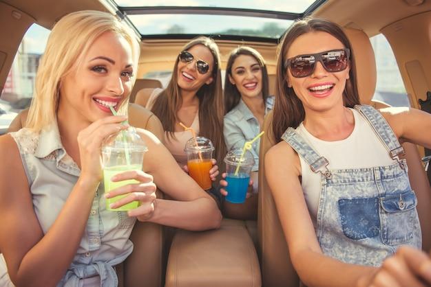 Stijlvolle meisjes cocktails drinken in een auto Premium Foto