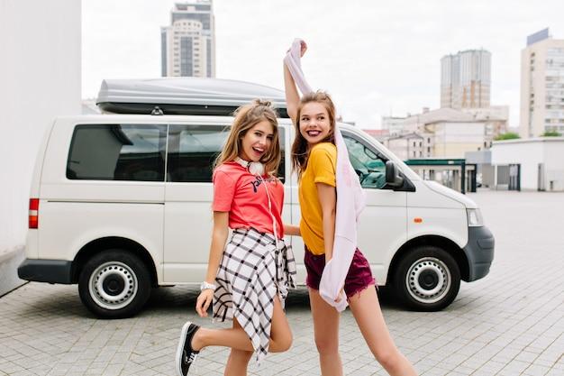 Stijlvolle meisjes in lichte trendy kleding dansen met een glimlach, samen buiten chillen Gratis Foto
