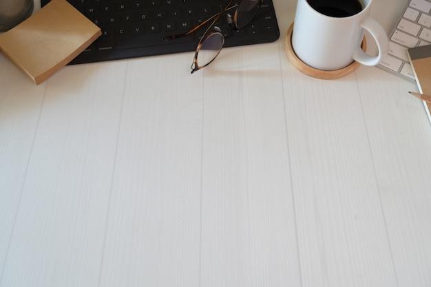 Stijlvolle, minimalistische werkplek met toetsenbord, notebook, kantoorbenodigdheden en kopieerruimte Premium Foto