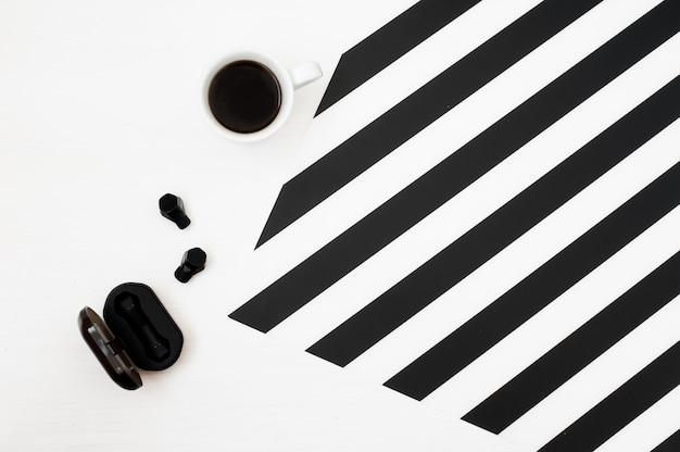Stijlvolle minimalistische werkruimte met kop koffie, draadloze oortelefoons Premium Foto