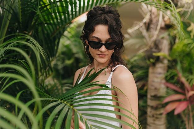 Stijlvolle moderne jonge vrouw met blond krullend kapsel, het dragen van zomerkleren wandelen onder de tropen in zonnige zomerdag. buiten foto van gelukkig lachend meisje heeft plezier en geniet van weekend Gratis Foto