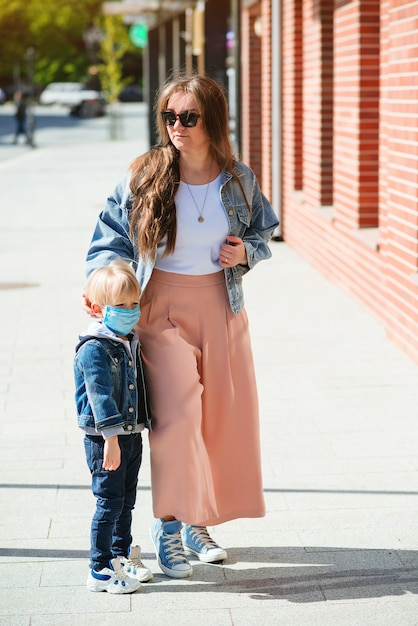 Stijlvolle moeder en kinderen op een wandeling tijdens de coronavirusepidemie. zomervakantie. Premium Foto
