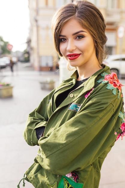 Stijlvolle mooie brunette op de zonnige straat Gratis Foto