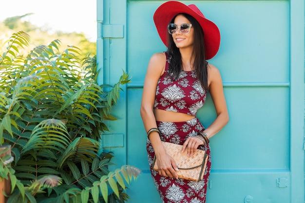 Stijlvolle mooie vrouw in rode hoed poseren op blauwe muur, gedrukte outfit, zomerstijl, modetrend, top, rok, mager, strooien handtas, zonnebril, accessoires, glimlachen, gelukkig, tropische vakantie Gratis Foto
