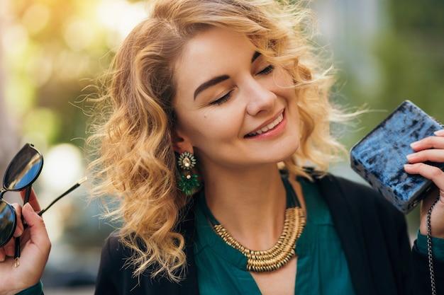 Stijlvolle mooie vrouw in spijkerbroek en jas lopen in straat met kleine portemonnee, elegante stijl, lente modetrends Gratis Foto