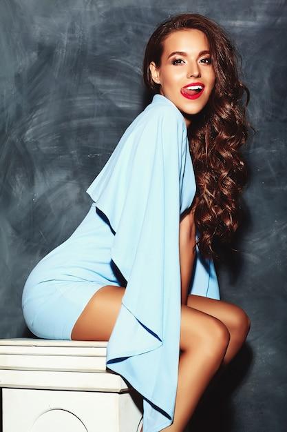 Stijlvolle mooie vrouw model met rode lippen in zomer heldere kleurrijke hipster blauwe jurk Gratis Foto