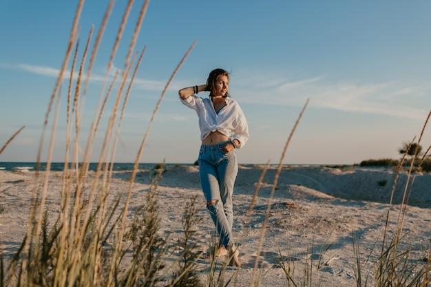 Stijlvolle mooie vrouw op zomervakantie op het strand, bohemien stijl, jeans Gratis Foto