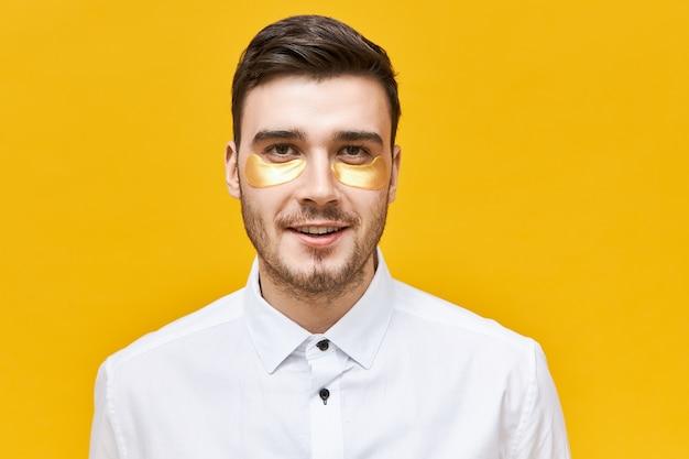 Stijlvolle ongeschoren jonge blanke man die een oogmasker draagt om uitdroging en donkere kringen aan te pakken vanwege een stressvolle levensstijl, poseren tegen een gele muur, Gratis Foto