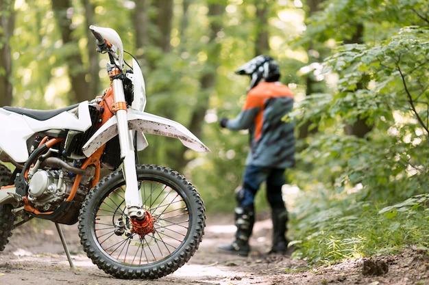Stijlvolle rijder met motor geparkeerd in het bos Gratis Foto