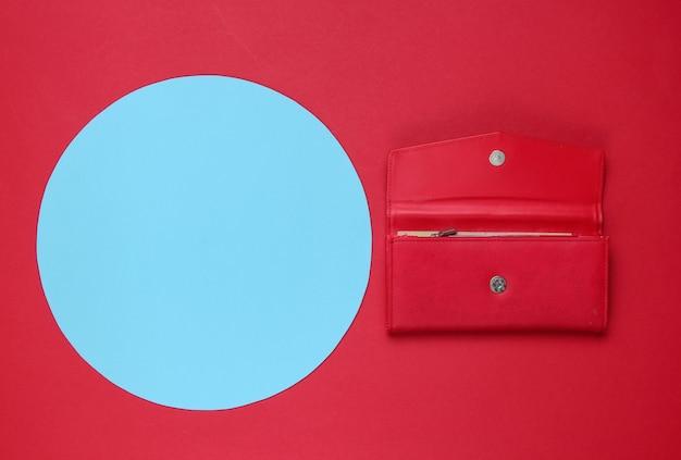 Stijlvolle rode lederen portemonnee voor dames op rode achtergrond met blauwe pastel cirkel voor kopie ruimte. creatief minimalistisch modestilleven. bovenaanzicht Premium Foto