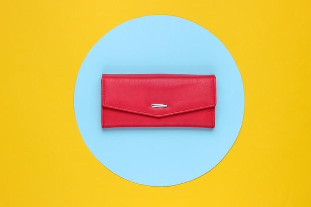 Stijlvolle rode leren damesportemonnee op gele achtergrond met blauwe pastel cirkel. creatief minimalistisch modestilleven. bovenaanzicht Premium Foto
