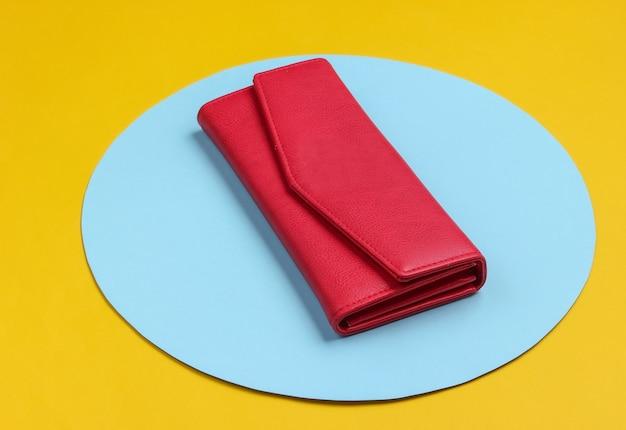 Stijlvolle rode leren damesportemonnee op gele achtergrond met blauwe pastel cirkel. creatief minimalistisch modestilleven Premium Foto