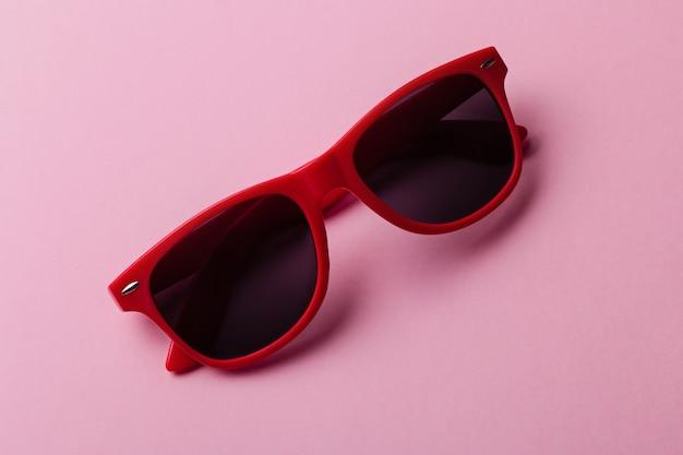 Stijlvolle rode zonnebrilclose-up op roze achtergrond Premium Foto