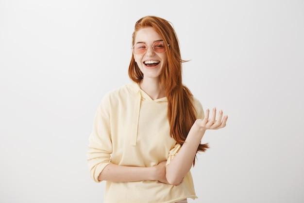 Stijlvolle roodharige vrouw in zonnebril lachen en gelukkig glimlachen Gratis Foto