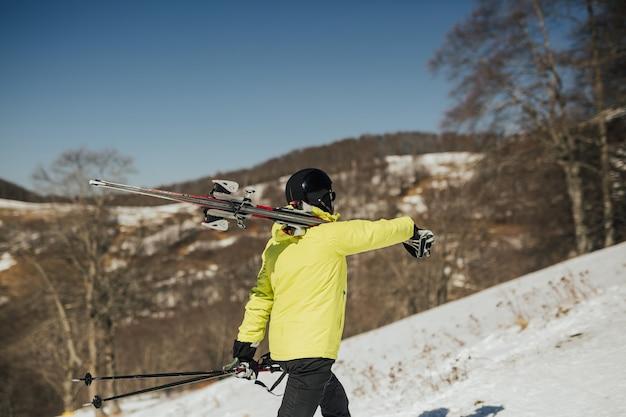 Stijlvolle skiër in een zwart skimasker en groen jasje gaat en houdt ski's op haar schouder Premium Foto