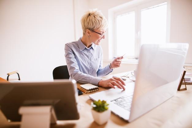 Stijlvolle succesvolle zakenvrouw online kopen met de kaart zittend in het mooie heldere kantoor. Premium Foto