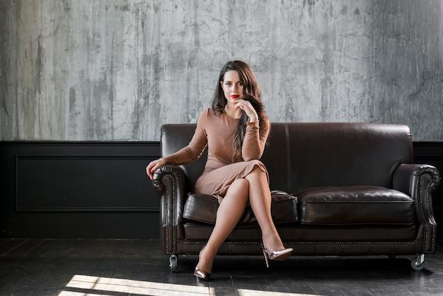 Stijlvolle trendy jonge vrouw met gouden hoge hakken zittend op een gezellige sofa Gratis Foto