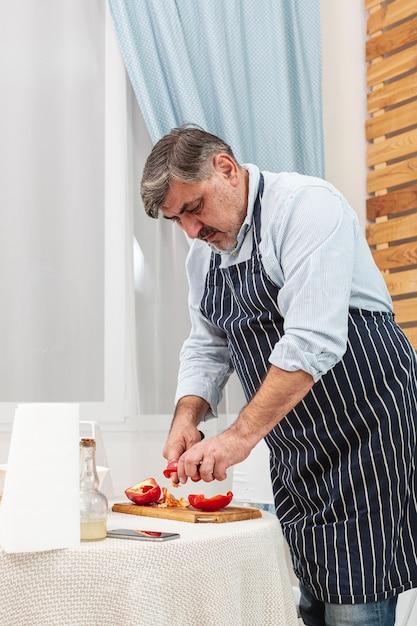Stijlvolle vader die tomaten snijdt Gratis Foto