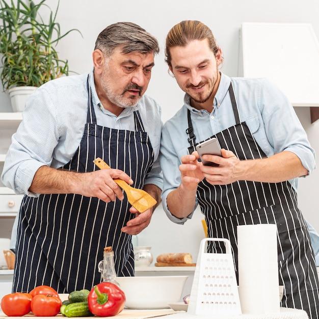 Stijlvolle vader en zoon kijken op telefoon Gratis Foto